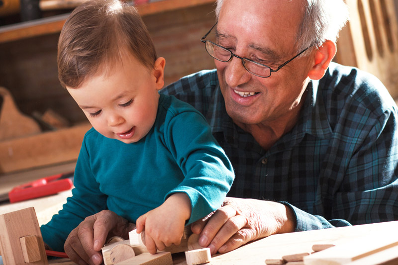 Grandpa helping young child with wooden blocks